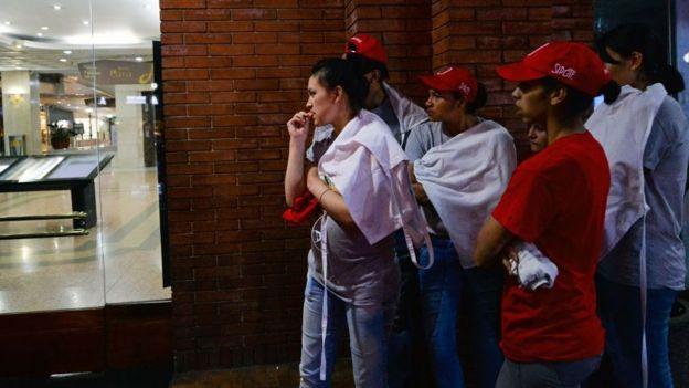 Gente afuera del centro comercial mirando el operativo.