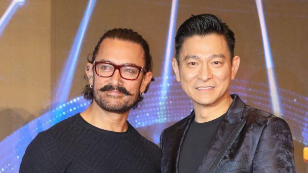 """4月15日,香港影視紅星劉德華和印度著名演員阿米爾·汗共同出席電影《神秘巨星》(香港譯名《打死不離歌星夢》)在香港舉辦的慈善見面會。香港天王與印度天王相遇,吸引大批""""粉絲""""前來,幾乎塞爆現場。"""