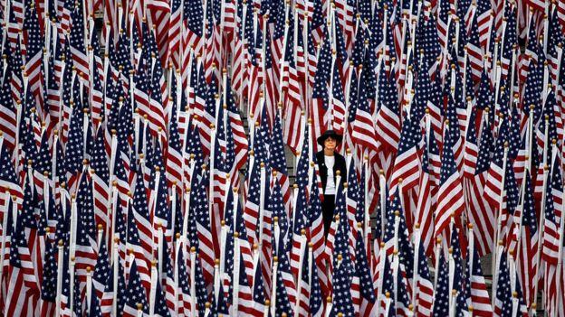 """Una mujer camina entre unas 3.000 banderas de EE.UU. que forman el """"Campo de Sanación"""" afuera del Pentágono, el 11 de septiembre de 2008, en Arlington, Virginia."""