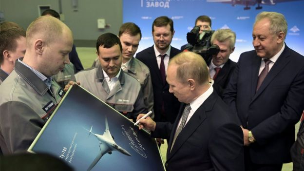 Russian President Vladimir Putin signs a picture of a TU-160M nuclear bomber