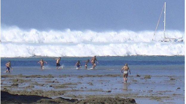 นักท่องเที่ยวกำลังวิ่งหนีคลื่นที่โถมเข้ามาเมื่อวันที่ 26 ธันวาคม 2547