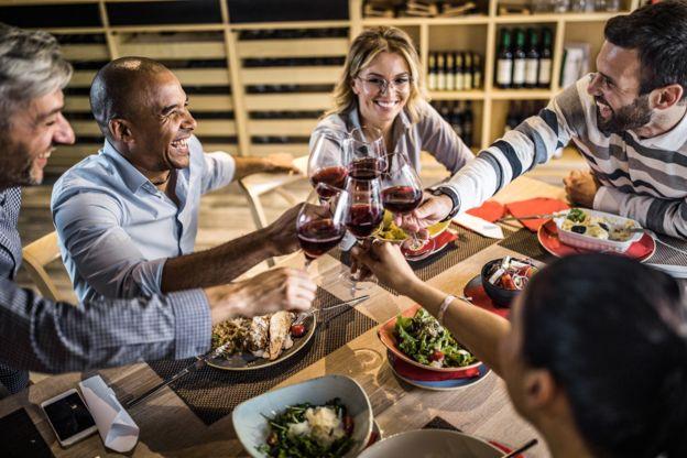 Un grupo de amigos brindando a la mesa