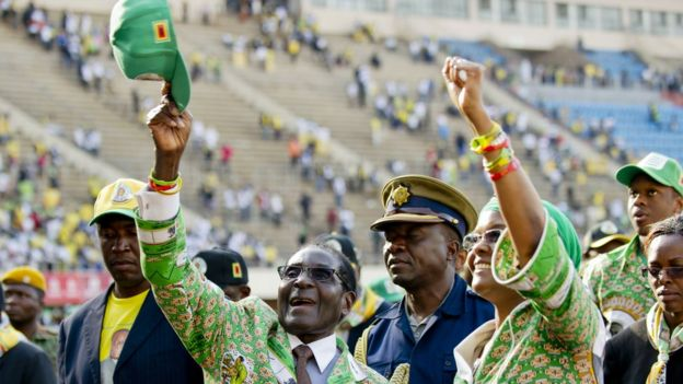Robert Mugabe (L) and his wife Grace (R) greet supporters after his address at a rally in Harare on 28 July 2013