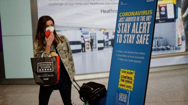 A passenger wears a mask in London's Heathrow Airport