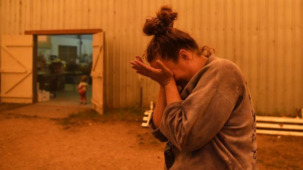 Jesse Collins organizando doações em um centro de evacuação na Austrália enquanto fala sobre o quão difícil é buscar água