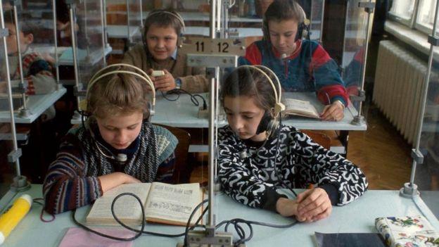 Crianças com fones de ouvido em sala de aula