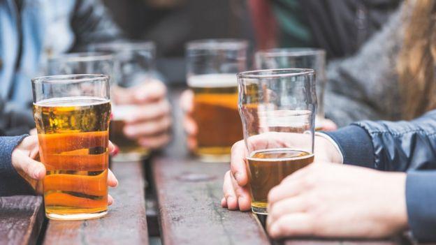 Pessoas segurando copos de cerveja