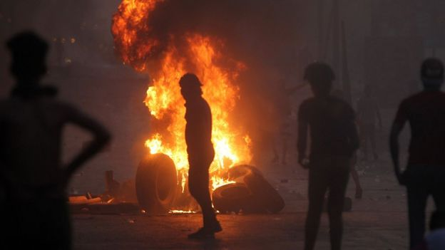 A man stands in front of a burning tyre