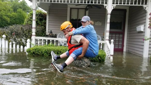 A Texas National Guard soldier carries a woman on his bank as they conduct rescue operations