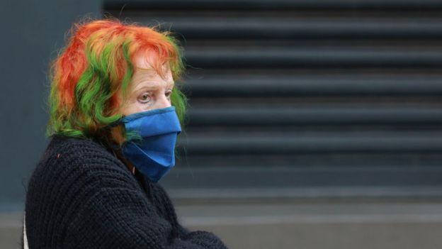 Mulher usando máscara na rua na África do Sul