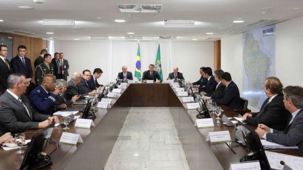 Bolsonaro, ministros e governadores em mesa de reunião