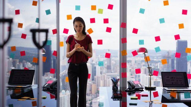 Mujer pegando papeles de recordatorio por toda su oficina