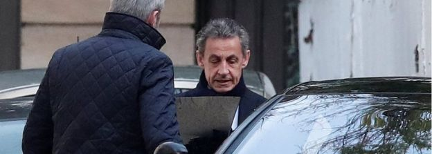 Former French President Nicolas Sarkozy enters his car as he leaves his house in Paris, 21 March 2018
