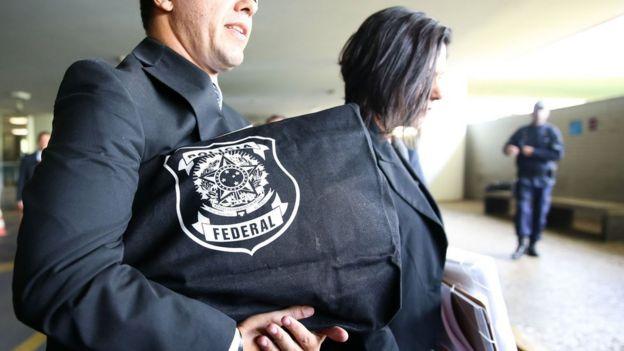 Agente carrega bolsa com emblema da Polícia Federal