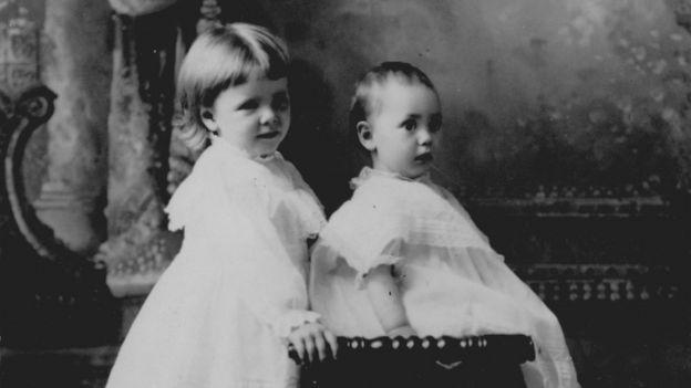Menina e seu irmão bebê usando vestido branco; fotografia de 1905, nos Estados Unidos