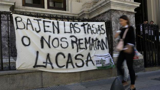 """""""Bajen las tasas o nos ramatan la casa"""" reza un cartel colgado en las rejas del Banco Central de Argentina"""