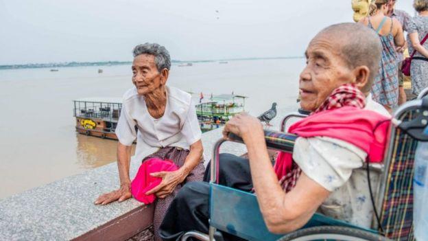 Bun Chea sentada em margem de rio ao lado de sua irmã na cadeira de rodas