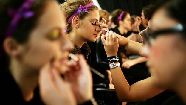 Imagem mostra mulheres sendo maquiadas