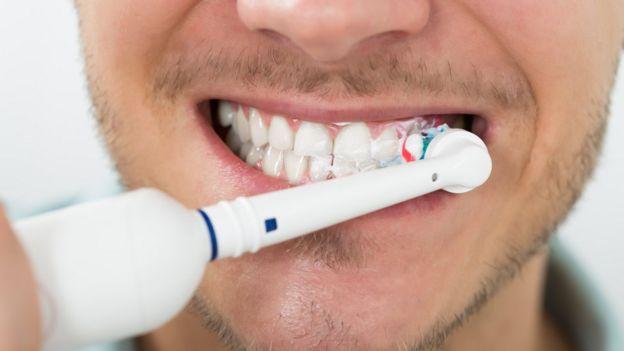 Homem usa escova de dentes elétrica