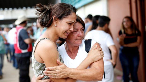Mulheres se confortam em meio a busca por desaparecidos