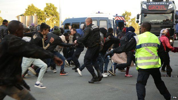 Migrants rush at a police cordon by a truck route along the perimeter fence of the Eurotunnel site at Coquelles in Calais, France on 30 July 2015