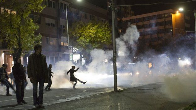 A protester kicks off a tear gas canister during clashes with Kosovo police in front of the central police station in Kosovo capital Pristina after the arrest of a prominent opposition politician Albin Kurti on Monday, Oct. 12, 2015.