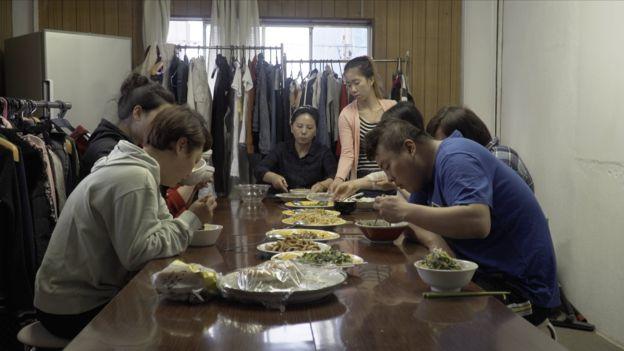 Trabajadores inmigrantes comiendo en un refugio en Japón.