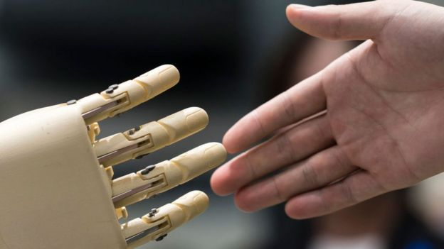 Una mano de robot y una mano humana a punto de estrecharse