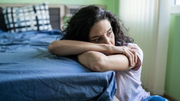 Una mujer triste al bode de la cama.