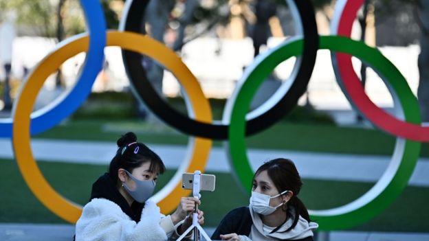 Mulheres japonesas com máscaras em frente a símbolo dos Jogos Olímpicos