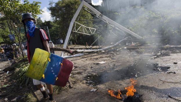 Un manifestante con un escudo improvisado que lleva la bandera de Venezuela pintada.