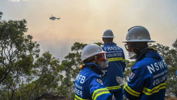 Firefighters use helicopters to dump water on the blaze