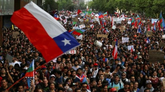 "Demonstrators march with flags and signs during a protest against Chile""s state economic model in Santiago, Chile October 25, 2019"