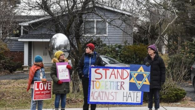 People show support to the Jewish community with banners