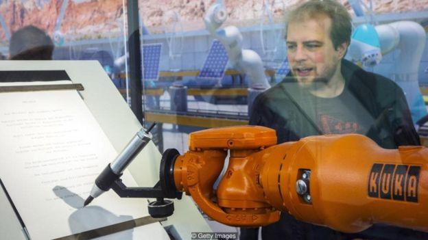 Homem olha para robô