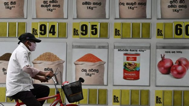 A msn wearign a facemaks cycles past a supermarket with food item prices along a street during a government-imposed nationwide lockdown as a preventive measure against the COVID-19 coronavirus in Colombo on March 30, 2020