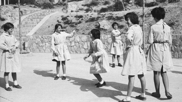 Un grupo de niñas jugando en el patio de un colegio.