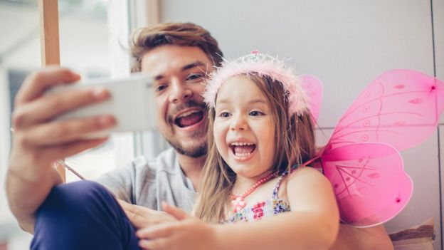 father and daughter using cellphone