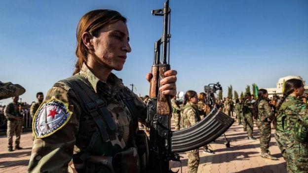 Kurdish fighter stands with gun at funeral in Derik on 13 October 2019