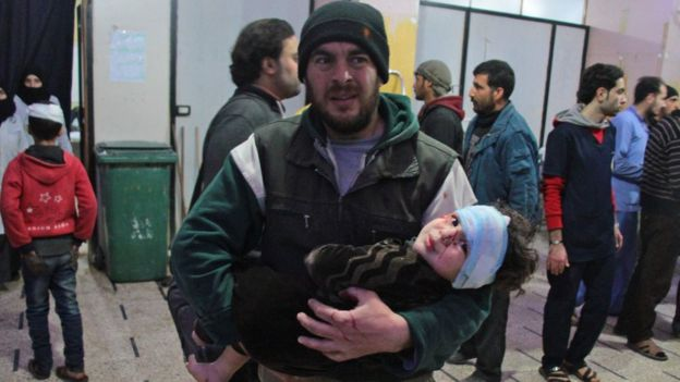 A Syrian man carries a wounded infant at a makeshift hospital in the rebel-held town of Douma, 20 February 2018