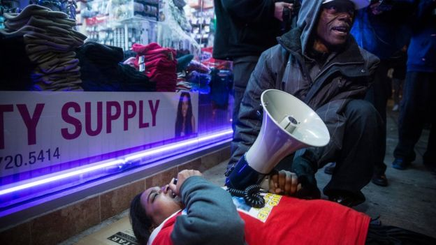 "Erica Garner pictured lying on the floor, leading a demonstration march and ""die in"" event"