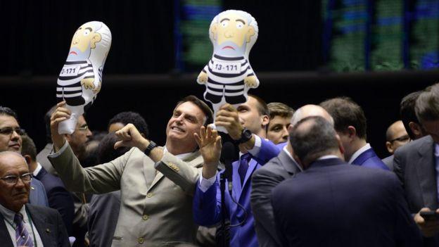 Jair Bolsonaro (esq.) e Eduardo Bolsonaro (dir.) com bonecos 'pixuleco' simbolizando o ex-presidente Lula preso