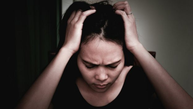 Una mujer se sujeta la cabeza y tiene cara de preocupación