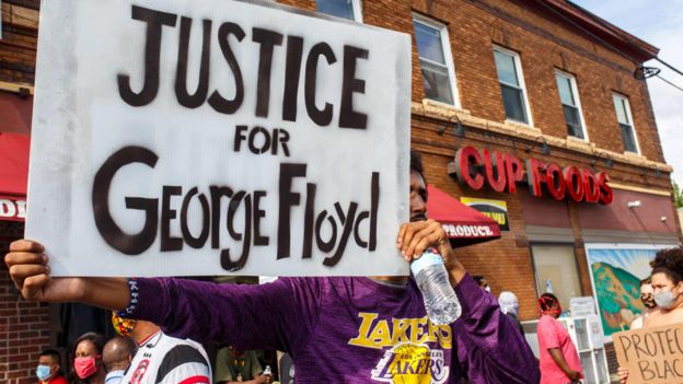 "Protester holding up a sign saying ""Justice for George Floyd"""