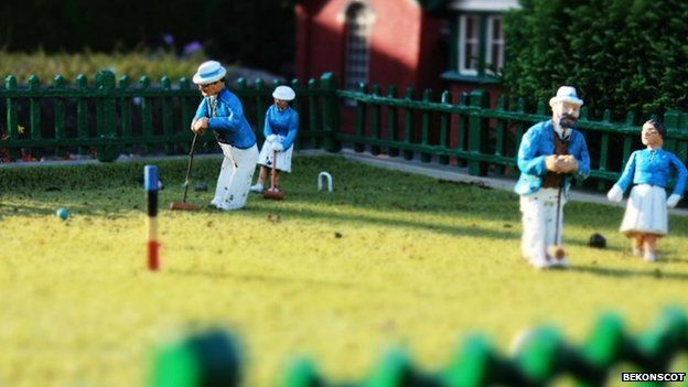 Model figures playing croquet