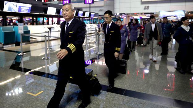 台湾桃园机场一队华航机组在机长带领下通过值机柜台(台湾中央社图片8/2/2019)
