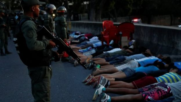 A security force member stands next to detainees on a street after looting during an ongoing blackout in Caracas, Venezuela March 10, 2019