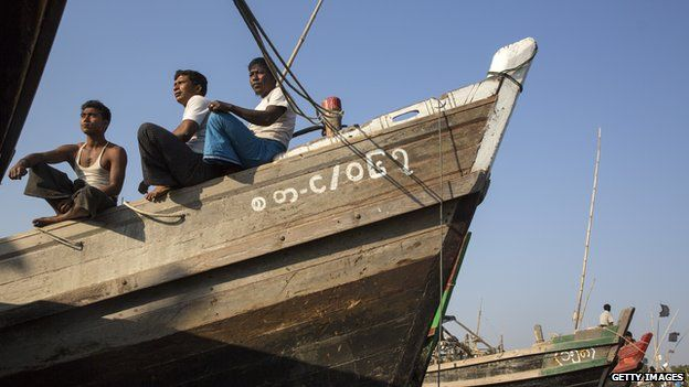 Rohingya fishermen relax on a fishing boat on a boat jetty in March 2015 near the Burmese town of Sittwe
