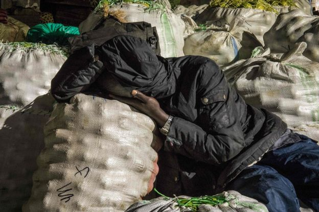 A trader sleeps next to items to be sold at a market following a directive from Ugandan President Yoweri Museveni that all vendors should sleep in markets for 14 days