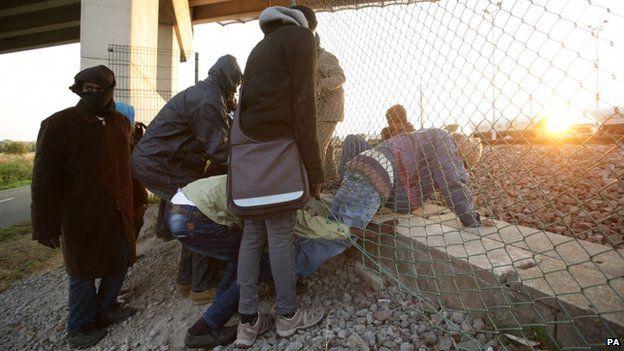 Migrants climb through a fence in Calais